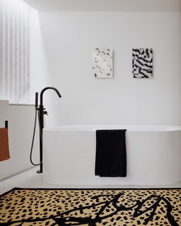 A bold black and white bathroom with a graphic leopard print rug.