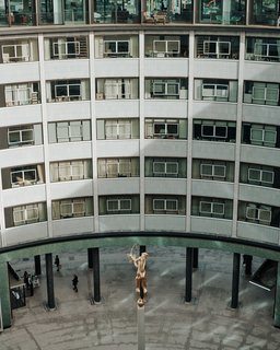 The ring-shaped building was formerly the BBC Television Center. A refurbished Helios statue stands in the courtyard.