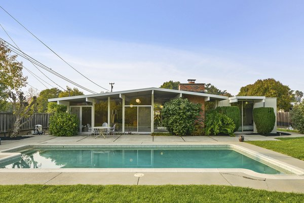 The backyard boasts a swimming pool, established fruit trees, and Concord grapes.
