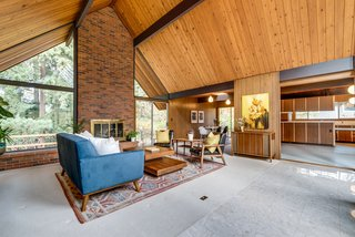 The open living plan features a cedar-paneled tongue-and-groove ceiling anchored by a brick fireplace.
