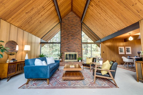 Dramatic floor-to-ceiling windows overlook the forested half-acre lot and bring the outdoors in.