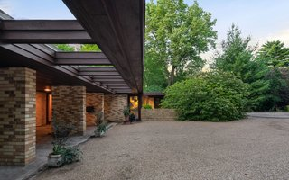 The flat roof cantilevers out over a stone walkway.