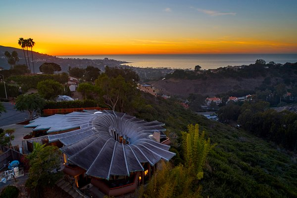 The Lotus House beautifully blends into the hillside when seen from above at night. The sculptural, organic forms seem to unfold—giving the home its name.