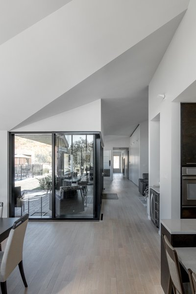 The roof's angular planes help unify the central living spaces under the multi-faceted ceiling.