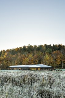 The Vallée du Parc Residence features a complex, angular roof that echoes the form of the surrounding hills.