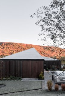The roof creates a dialogue with the surrounding landscape through multiple sloped planes, irregular lines, and an absence of overhangs. The home's form appears to change according to one's angle of approach.