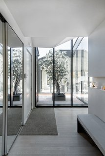 Floor-to-ceiling walls of glass flood the interior with natural light while providing views of a courtyard-like terrace with a tree.