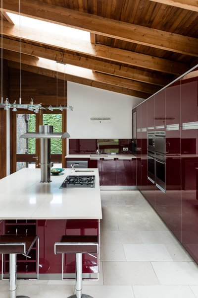 The modern kitchen with glossy, red cabinets is spacious with ample storage and a center island with seating.