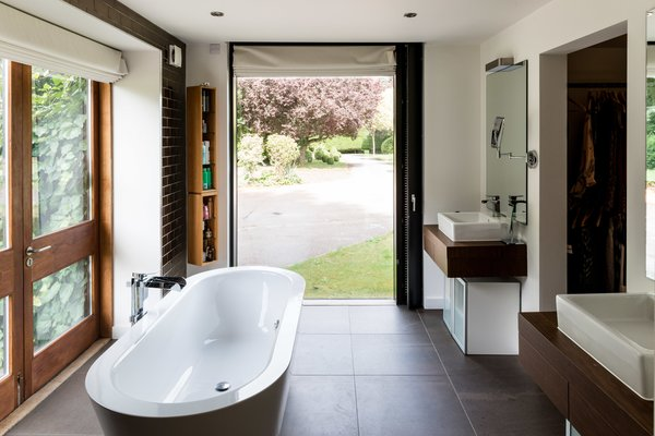 The ensuite master bath features a freestanding tub, and more floor-to-ceiling glazing affords lush views across the gardens.