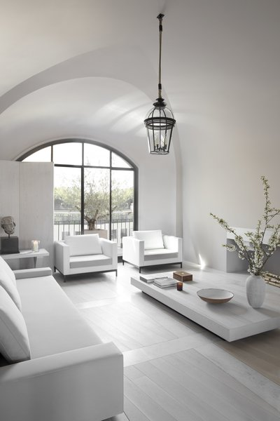 The vaulted ceiling creates a grand sense of space. The large window was inspired by an old door the designer saw on a trip to Oxford, England.