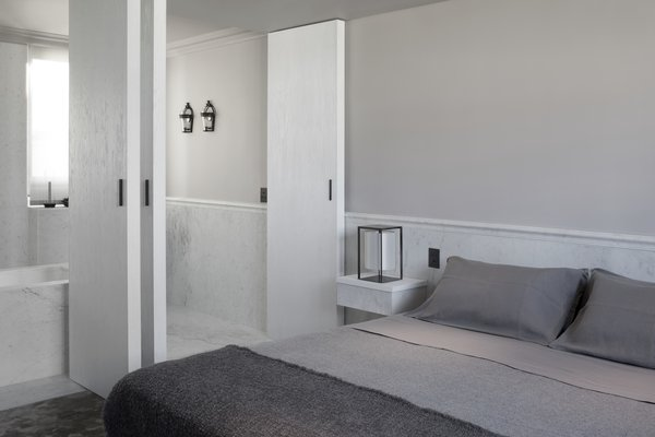 In the master suite, handcrafted, double-pivot doors in a brushed ash finish create an ensuite bathroom that can be fully opened up or closed off. Carrara marble molding outlines the room and provides an extravagant touch.
