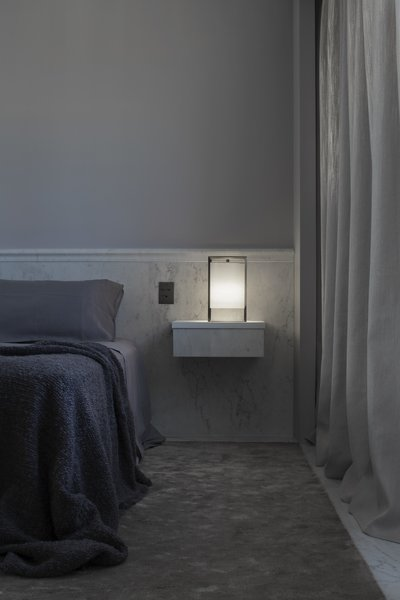 The brass bedside lamp with a silk lampshade designed by Alan sits on a marble and ash wood floating nightstand.