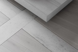 A detail of the light grey brushed oak floors with marble accent lines.