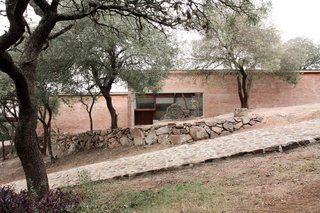 The first outcropping of rocks has been incorporated into the home's entrance, which is set adjacent to a rustic, stone road.