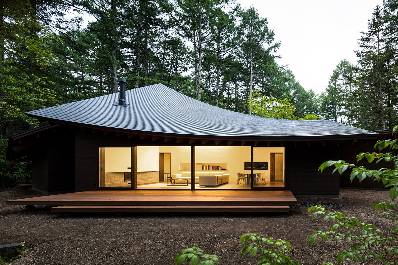 Exterior, Curved RoofLine, Wood Siding Material, House Building Type, and Shingles Roof Material Located in Karuizawa, a popular summer resort town in Japan's Nagano Prefecture, Four Leaves is a weekend getaway designed to accommodate the homeowner and their guests in a lush, sylvan setting. Designed by Kentaro Ishida Architects Studio (KIAS), the highlight of the stunning, 2,400-square-foot house is its sloping, angular roof sections that are delicately assembled to resemble fallen leaves.  Photo 2 of 21 in Dwell's Top 10 Home Tours of 2019 from This Serene Japanese Retreat's Overlapping Roofs Look Like Fallen Leaves