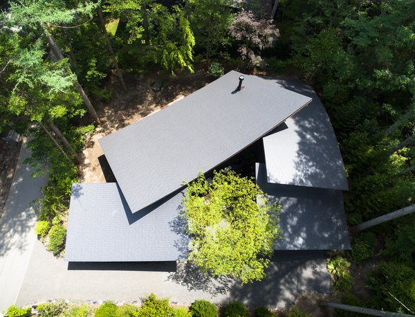 Viewed from above, the home wraps around itself and is folded around a small central courtyard. The roof sections overlap in an organic way, giving the home its name: Four Leaves.