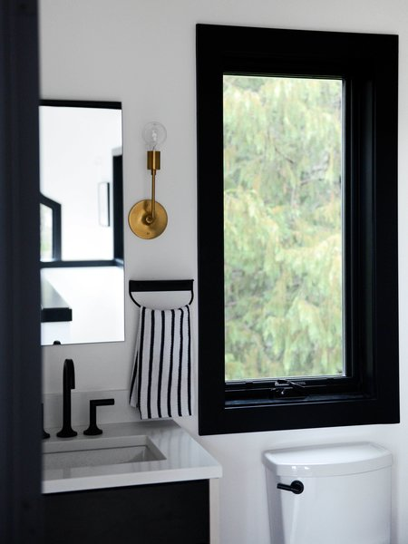The bathroom features an Astrid Sconce with a natural brass finish from Schoolhouse.