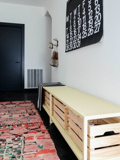 The entryway is designed for gear management with hooks and a custom-made bench with storage baskets. The floors are made of durable, hospital-grade FLEXCO radial high-profile rubber. The colorful rug from Kat + Maouche softens up the stark interior.