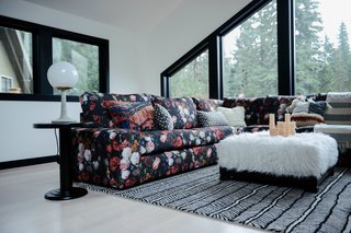 The living area is layered with prints and textures—including a bespoke sofa print inspired by a Dutch masterpiece from the Rijksmuseum. The herringbone rug, side table, and Matter Lamp are from Schoolhouse. The ottoman is from Pottery Barn Kids.