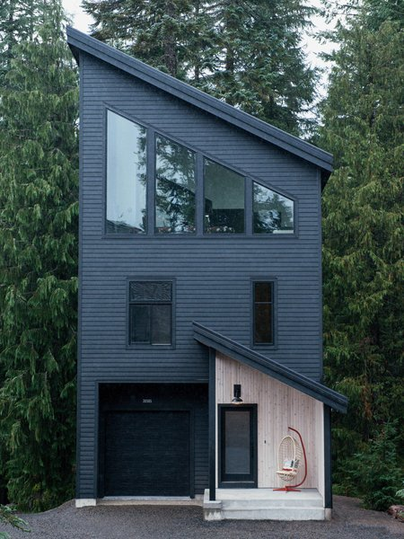 Oliver and Sara Fritsch's Mount Hood getaway—not far from Mount Hood Meadows, one of the largest ski resorts in Oregon—is tall and skinny, reminiscent of the canal houses in Amsterdam, where the Fritsch family lived for three years. Also notable is the facade, painted in a custom shade of soft black. Inside, the house is arranged in a reverse layout, with the open living space located at the top.