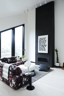 The open-plan living space is anchored by a black brick fireplace with a sleek modern profile. Muddox makes the commercial wire-cut thin bricks in ebony with liquid black added to the mortar mix. The Studio Floor Lamp is from Schoolhouse.