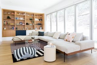 Myers designed a new built-in bookcase that floats in the wall. The color and style of the built-in match the kitchen cabinets, helping to integrate the spaces and create flow. The L.A. Rivera sectional from Croft House is paired with a stripe rug from Hem and a Scamp coffee table from Blu Dot.