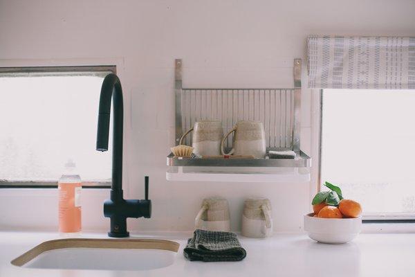 The minimalist kitchen features chic ceramics and a matte black faucet.