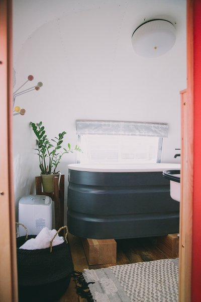 The trailer is hooked up to running water, however it features a waterless composting toilet from Separett. In the winter, there is on-demand hot water for luxurious bathing. The deep, repurposed stock tank tub is one of the couple's favorite things about the renovation.