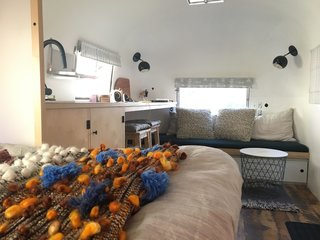 The couple efficiently divided the space to create fully functional zones. This view is from the bed looking towards the other end of the Airstream.