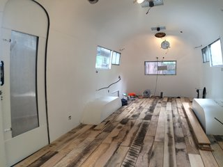 The reclaimed Settlers' Plank flooring is from Pioneer Millworks. It consists of a mosaic of hardwood species precision milled in a tongue and groove format that allowed the couple to install the floor themselves. The couple also decided to finish the floors themselves—this photo was taken before the finishing.