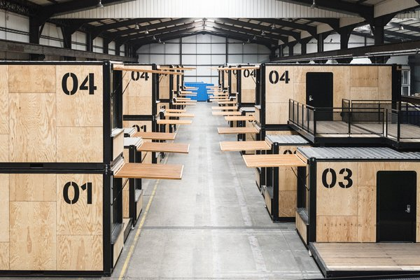 The mobile hotel rooms are made from repurposed shipping containers. Here they are shown stacked in a warehouse and ready to be deployed.