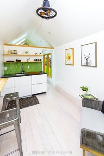 The minimalist open kitchen/dining/living room features a mostly neutral palette. A green tile backsplash provides a pop of color.