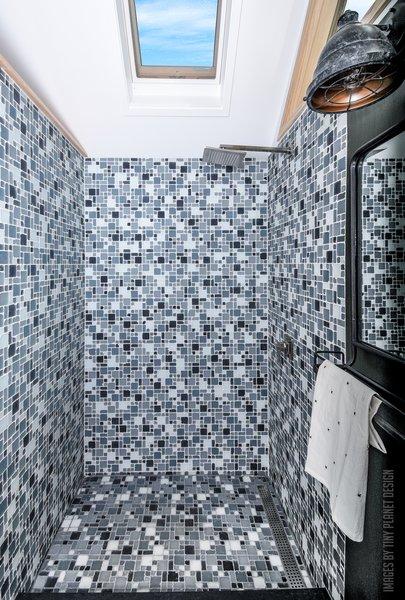 The luxury bathroom boasts a stylish glass-tiled shower and a solar-vented skylight.