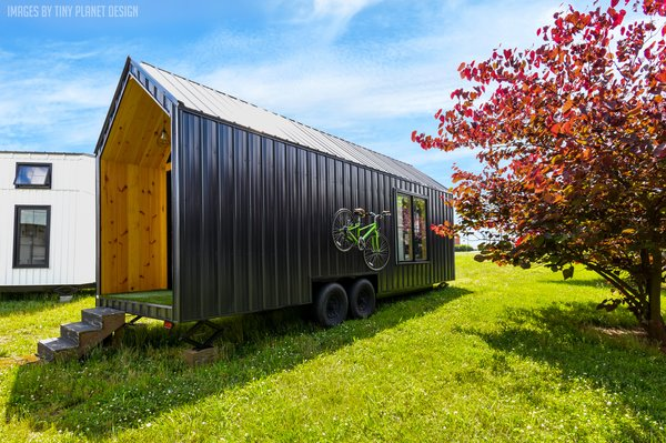 """The Roost26 tiny house features a lightweight, black AG metal roof and facade with a """"detachable garden"""" on one side and bike racks on the other."""