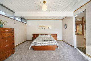 The bedrooms feature new carpeting and original, midcentury lighting.