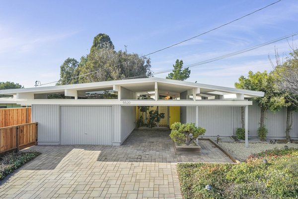 The classic Eichler facade has recently been painted and features a yellow door for a fun pop of color.