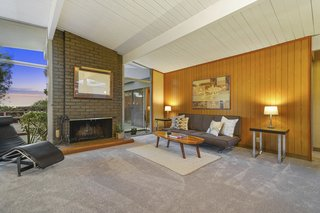 The open-plan living space features a strong brick-inlay fireplace and original wood paneling.