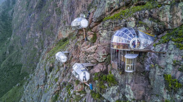 Skylodge Adventure Suites are luxury dwellings affixed to the mountainside in Peru's Sacred Valley, approximately nine miles north of Cusco. Visitors interested in staying at Skylodge must climb a quarter of a mile of protected trails and fly through the sky on zip lines.
