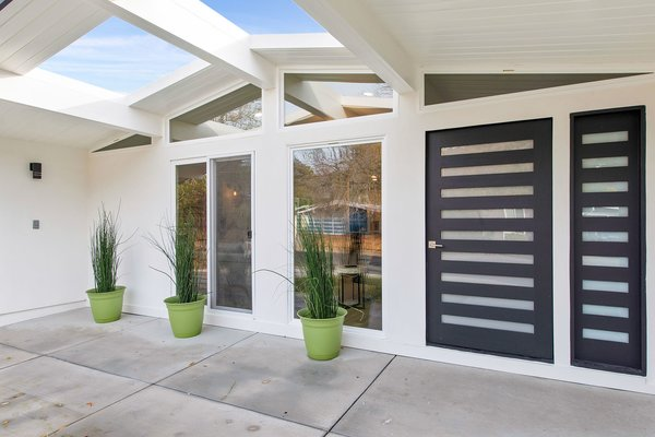 The entry features a covered patio, new doors, and full-height windows.