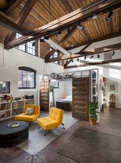 The living area features high ceilings with exposed rafters and lots of natural light.