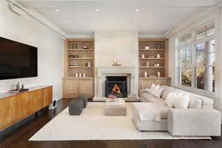 The TV nook sits just off the living room. Built-in shelving flanks a cozy fireplace.
