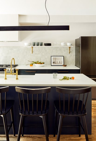A linear modern light fixture by AlexAllen Studio hangs above the center island. Black Windsor counter stools from Target complete the center island's breakfast bar. The shiny brass faucet and shelf brackets are both from Rejuvenation. The beautiful glazed Moroccan zellige tiles are from Cle, and the countertops are Ceasarstone.