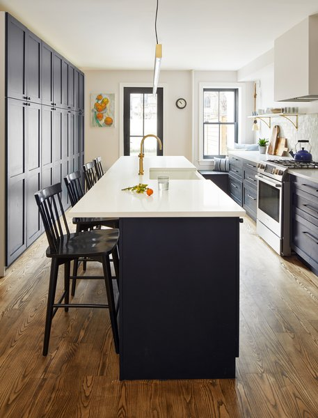 Instead of adding counter space on both sides of the kitchen, Wooden opted for floor-to-ceiling cabinets, which provide ample storage space and help keep the kitchen tidy. A center island provides additional storage, prep space, and a breakfast bar. At the back, a classic black panel window and patio door lead to the family's outdoor space while bringing much-needed natural light into the formerly dark kitchen.