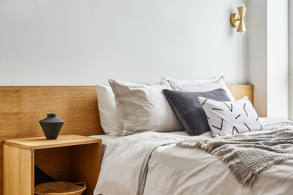 """A bedroom in """"Baller Jawn."""" The custom bed is by Farmhaus Modern. The striped blanket is from Thom Roland, and the printed pillows are by Flax and Symbol."""