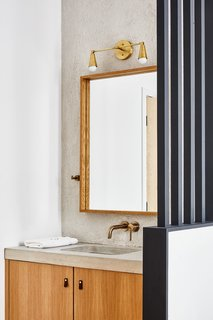 The bathroom vanity features a concrete counter from 1025 Studio, a mirror from Kenneth Miller, and lighting by Noevara.