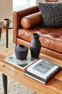 The coffee table is from Farmhaus Modern, and the black stepped planters are from Cone 10.