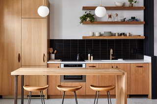 The kitchen cabinets were designed by True Hand Society and fabricated by Summus with leather cabinet pulls from Peg & Awl for an earthy feel. The floating shelves are from Lostine. The bar stools are from Leeward, and the pendant lighting is by Noevara.