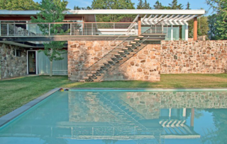Inside and out, the home displays a rich mix of natural materials. A stairway cantilevers from the fieldstone wall and leads to the pool.