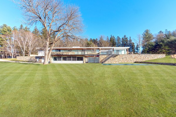 The midcentury modern home is located on 1.7 acres of land and features bluestone terraces, fieldstone walls, and elevated views of the countryside.