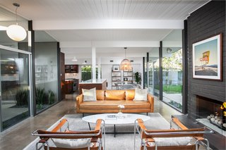 The open-plan living space is anchored by a brick-inlay fireplace, typical of Eichler homes.